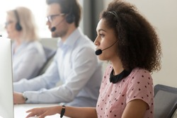 Multiracial call center workers sitting at workplace looks at computer screen use telephone with headset, focus on mixed race side view millennial woman providing quality affordable assistance concept