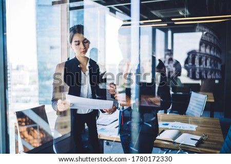 Multiracial colleagues in formal outfit communicating and discussing project on paper while standing in contemporary office through transparent window