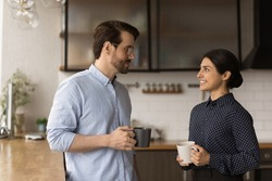 Multiracial colleagues talk during lunch break in office kitchen. Indian woman communicates with workmate hold coffee cups enjoy conversation, discuss work or personal. Good relations at work concept