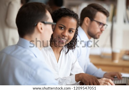Multiracial colleagues talk sitting together at shared table, discuss business ideas or project, diverse employees communicate in coworking space, chatting or explaining something. Cooperation concept
