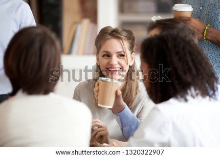 Multiracial company members sitting in workplace, colleagues friends take a break during working day drinking coffee at paper carton cups and chatting, focus on smiling attractive female team leader