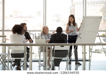 Multiracial company team diverse staff gathered at boardroom together for brainstorming negotiating. Business people listen skilled coach. Business plan startup, effective marketing strategy concept
