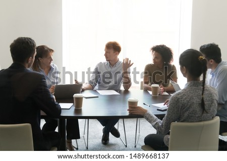 Multiracial employees discuss company project drinking coffee in conference room, diverse workers talk negotiate brainstorming at shift meeting in office, have tea break together. Teamwork concept