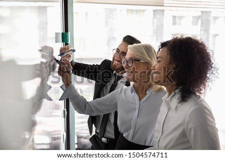 Multiracial entrepreneurs work on common task business plan strategizing together thinking on start up new ideas, team led by 50s creative manager african arabian subordinates take part use flip chart