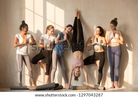 Multiracial excited girls in sportswear stand near wall wait for yoga class having fun together, happy sportive female yogi entertain play childish practicing poses, have break in training or workout