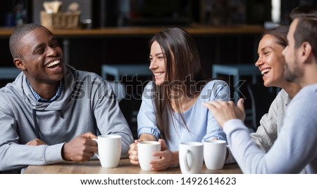 Photo of Multiracial friends girls and guys having fun laughing drinking coffee tea in coffeehouse, happy diverse young people talking joking sitting together at cafe table, multicultural friendship concept