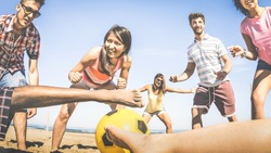 Multiracial friends group playing beach soccer at beginning of summer - Concept of multi cultural friendship fun and sport against racism - Vintage filter look with main focus on asian girl near ball