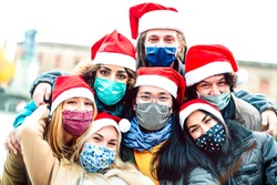 Multiracial friends taking selfie wearing face mask and santa hat - New normal Christmas holiday concept with young people having fun together outdoors - Bright filter with focus on central asian guy