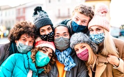Multiracial friends taking selfie wearing face mask and winter clothes - New normal lifestyle concept with young people having fun together outside - Bright filter with focus on central asian guy