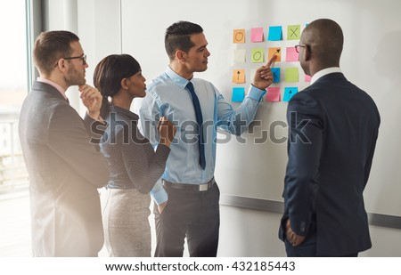 Multiracial group of colleagues discussing a business plan standing around a set of colorful memo notes stuck on the wall #432185443