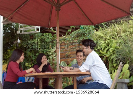 Multiracial group of four asian friends having a coffee together. Two women and two men at cafe, talking, laughing and enjoying their time. Lifestyle and friendship concepts #1536928064