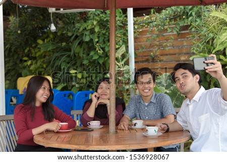 Multiracial group of four asian friends having a coffee together. Two women and two men at cafe, talking, laughing and enjoying their time while taking group selfie. #1536928067