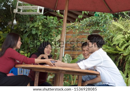 Multiracial group of four asian friends having a coffee together. Two women and two men at cafe, talking, laughing and enjoying their time. Lifestyle and friendship concepts #1536928085