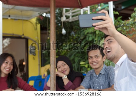 Multiracial group of four asian friends having a coffee together. Two women and two men at cafe, talking, laughing and enjoying their time while taking group selfie. #1536928166