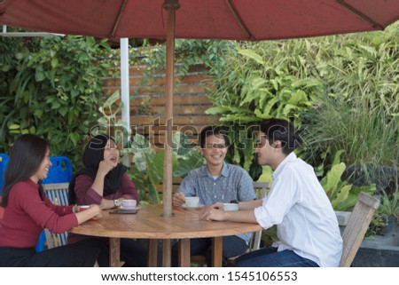 Multiracial group of four asian friends having a coffee together. Two women and two men at cafe, talking, laughing and enjoying their time. Lifestyle and friendship concepts #1545106553