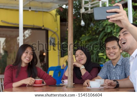 Multiracial group of four asian friends having a coffee together. Two women and two men at cafe, talking, laughing and enjoying their time while taking group selfie. #1545106604