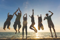Multiracial group of people jumping at beach. Backlight shot. Happiness, success, friendship and community concepts.