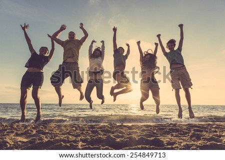 Multiracial group of people jumping at beach. Backlight shot. Happiness, success, friendship and community concepts. #254849713