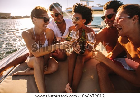 Multiracial group of people toasting drinks on the yacht deck and laughing. Cheerful men and woman partying on a boat.