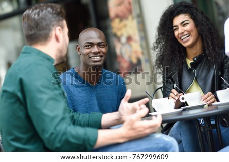 Multiracial group of three friends having a coffee together. A woman and two men at cafe, talking, laughing and enjoying their time. Lifestyle and friendship concepts with real people models #767299609