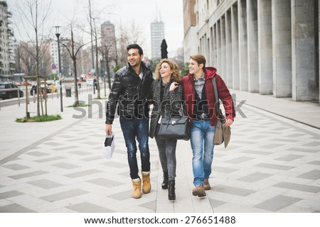 Multiracial group of two men and woman friends outdoor in town happy walking hugging #276651488