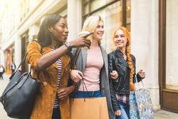 Multiracial group of women shopping and walking in London. Three girls, mixed race group, having fun in the city while shopping. Best friends sharing happy moments together