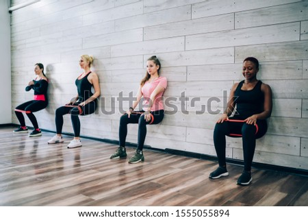 Multiracial group of young athletic slim women doing static exercise with rubber bands leaning on wall of gymnasium in squat Foto stock ©
