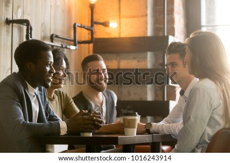Multiracial happy friends talking and drinking coffee sharing coffeehouse table, diverse african and caucasian millennial young people smiling enjoying pleasant conversation in cafe at coffee break