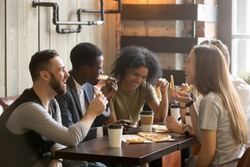 Multiracial happy young people eating pizza in pizzeria, black and white cheerful mates laughing enjoying meal having fun sitting together at restaurant table, diverse friends share lunch at meeting