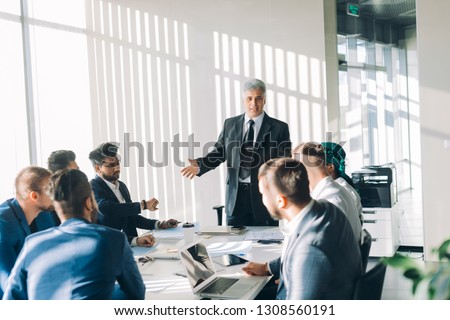 Multiracial male business executives discussing project sitting at conference table in spacious hall with panoramic city scapes, all men dressed in formalwear and have positive mood #1308560191