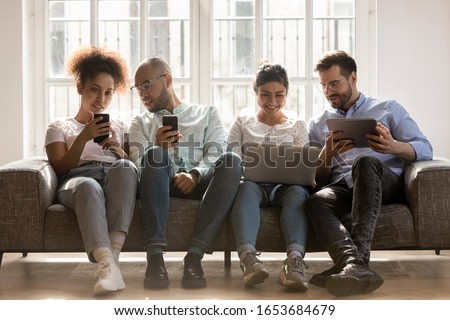 Multiracial mates sitting on sofa with modern electronic devices, friends using laptop tablet and cellphone having fun online using new app generations addicted with gadgets everyday overuse concept stock photo