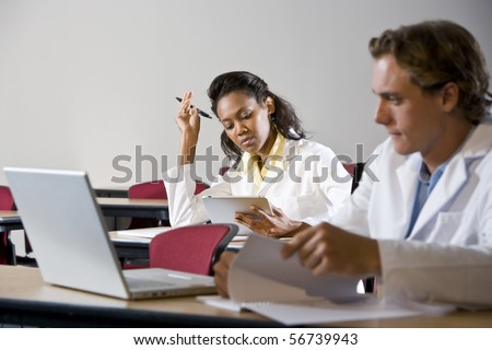 Multiracial medical students wearing lab coats studying in classroom