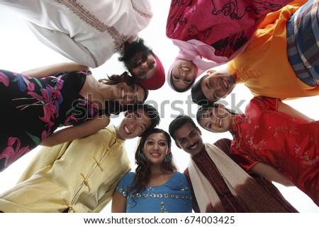 Multiracial men and women standing in a circle, posing at camera