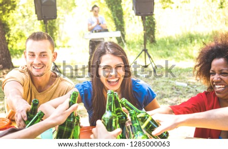 Multiracial millenial friend having fun at barbecue garden party with music - Friendship concept with young happy people toasting beer bottle at summer hangout - Guys and girls on warm sunshine filter