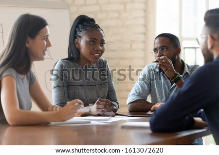 Multiracial millennial business partners talk discuss cooperation at meeting in office, diverse young businesspeople brainstorm consider paperwork share ideas at team briefing, collaboration concept