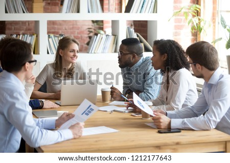 Multiracial millennial colleagues brainstorm discussing startup ideas during briefing in boardroom, female CEO hold business meeting with diverse employees, negotiating analyzing report or stats