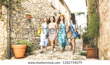 Multiracial millennial girlfriends walking in old town tour - Happy girl best friends having fun around city streets - University women students on travel vacations - Bright desaturated vintage filter