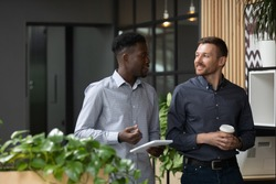 Multiracial millennial male colleagues stand having coffee break discussing startup project sharing business ideas in office, multiethnic man coworkers businessmen talk brainstorm at workplace