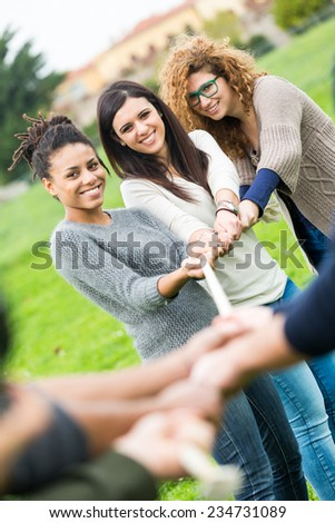 Multiracial People Playing Tug of War. Three Women playing against Three Men and Looking at them