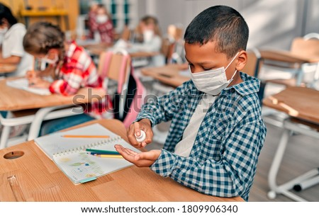 Multiracial pupils of primary school are ready to study after Covid-19 quarantine and lockdown. Children in class room wearing face masks and using antiseptic for coronavirus prevention.