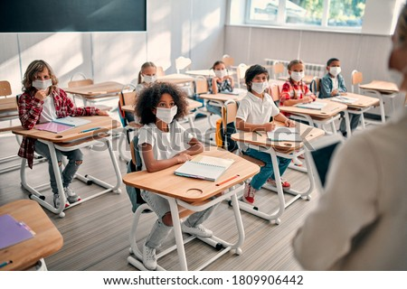 Multiracial pupils of primary school are ready to study after Covid-19 quarantine and lockdown. Children in class room with teacher wearing face masks and using antiseptic for coronavirus prevention.