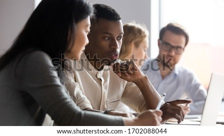 Multiracial serious colleagues sit at desk talk brainstorm using computer cooperate at office briefing, serious diverse coworkers speak discuss business ideas at boardroom meeting together