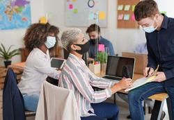 Multiracial staff at work in office while wearing surgical face mask - Dividers on the table for safety measures at work places