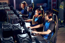 Multiracial team of professional cybersport gamers wearing headphones participating in global eSport tournament, playing online video games, side view