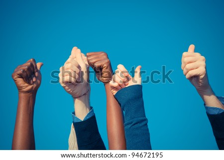 Multiracial Thumbs Up Against Blue Sky