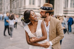 Multiracial wedding couple. Wedding in Florence, Italy. Caucasian groom hugs from behind African-American bride at Piazza del Duomo.