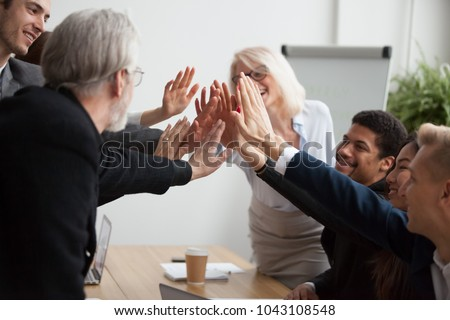 Multiracial young and senior business people join hands giving high five together, motivated diverse team showing team spirit synergy in goal achievement, promising help, supporting unity in teamwork