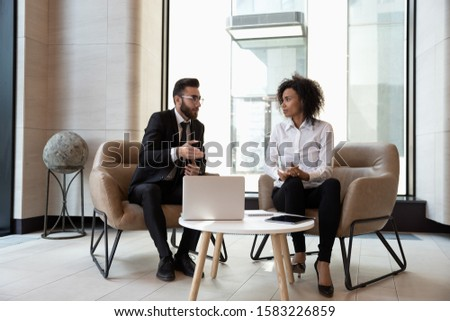 Multiracial young business partners sit in modern office cooperate working on laptop discussing ideas, concentrated motivated multiethnic businesspeople consider collaboration, partnership concept