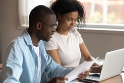 Multiracial young couple sit at table at home managing paperwork financial documents consider family expenditures together, multiethnic husband and wife pay household taxes or bills on laptop online