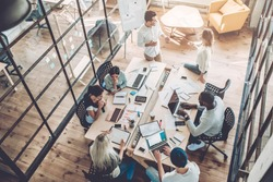 Multiracial young creative people in modern office. Group of young business people are working together with laptop, tablet, smart phone, notebook. Successful hipster team in coworking. Freelancers